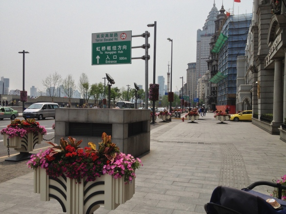 Flowers line the street that is next to the Bund.